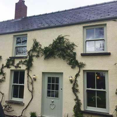 Chartwell green sash windows on cream house