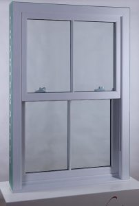 a white sash window with astragal bars on a white plinth