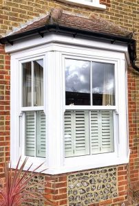a white bay window with shutters fitted in a brick house