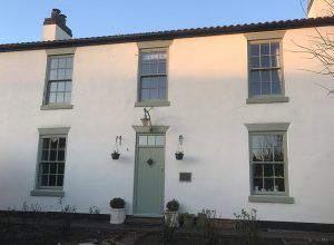 Grey sliding sash windows installed in a cottage