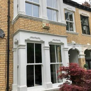 two sliding sash windows fitted in a two storey house with beige brick