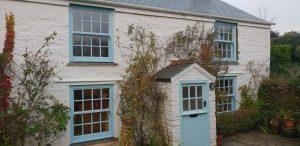 Blue heritage rose windows on white cottage