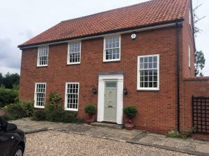 white ultimate rose sash windows on red brick house